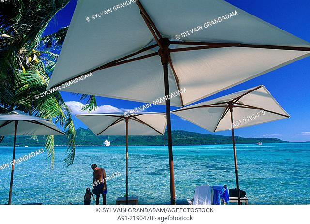 FRENCH POLYNESIA.LEEWARD ISLANDS.TAHAA ISLAND.LANDSCAPE AND WHITE SUNSHADES AT FORE