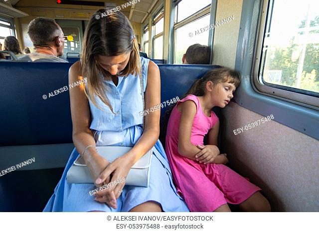 Tired mother and daughter sleep soundly in an electric train