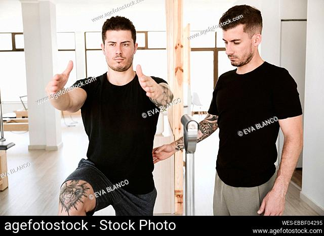 Male instructor supporting man exercising at pilates studio