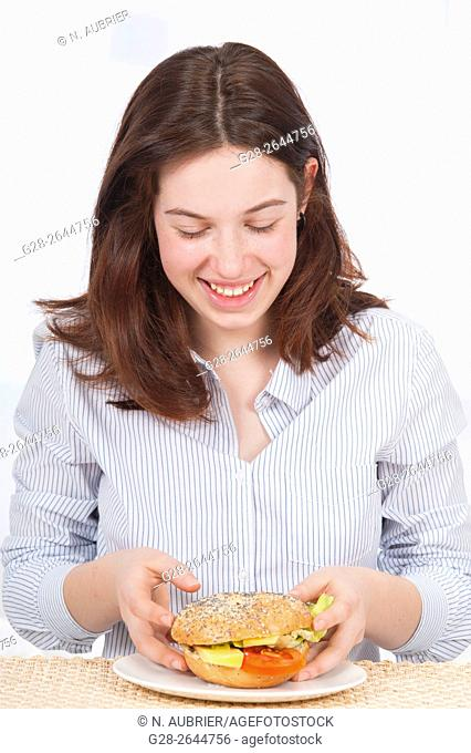 Smiling teenage girl about to eat a bagel at home