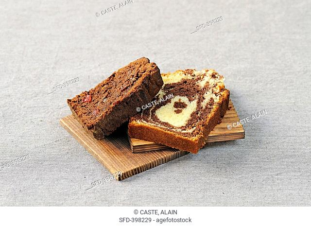 A piece of chocolate fruit cake and a piece of marble cake