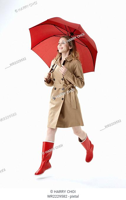 Young smiling woman wearing red umbrella, trenchcoat and red boots running