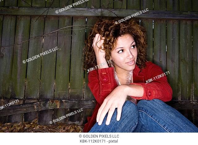 Portrait of young woman with hands running through her hair, sitting against a wooden fence