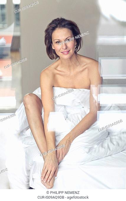 Portrait of mature woman sitting up in bed wrapped in bed sheet