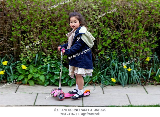 A Child Playing On Her Scooter, Sussex, UK