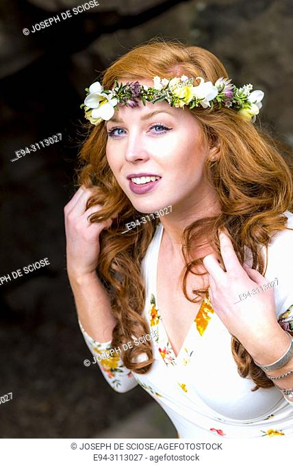 A pretty 25 year old redheaded woman wearing a crown of flowers and pulling her hair looking at the camera, outdoors