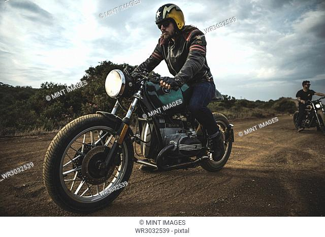 Man wearing open face crash helmet and sunglasses riding cafe racer motorcycle on a dusty dirt road