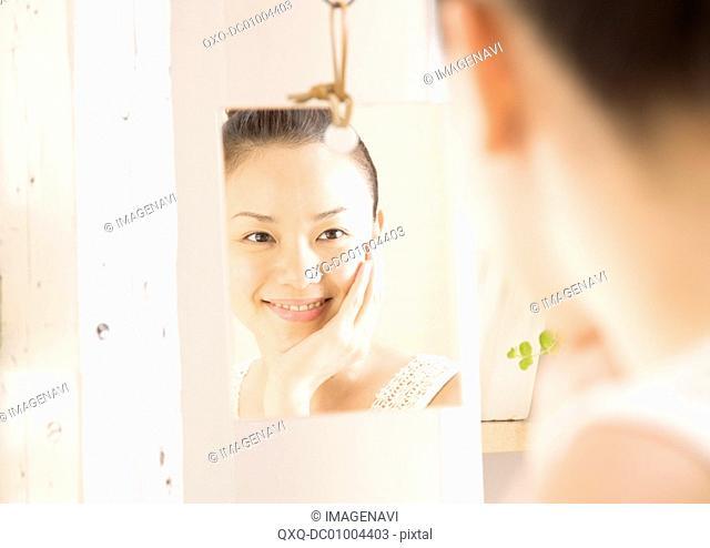 A woman looking at mirror