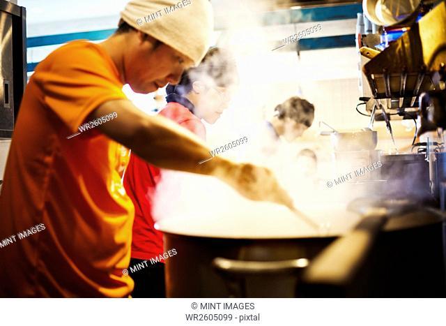 The ramen noodle shop. A chef stirring a huge pot of noodles cooking
