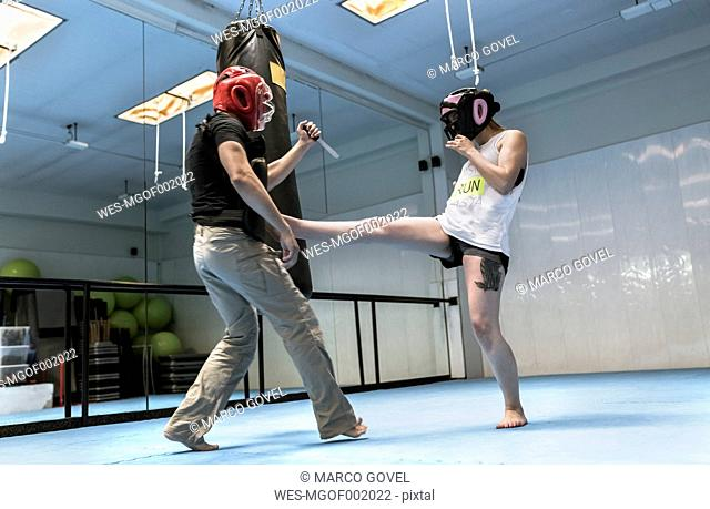 Young woman in gym doing self defense training
