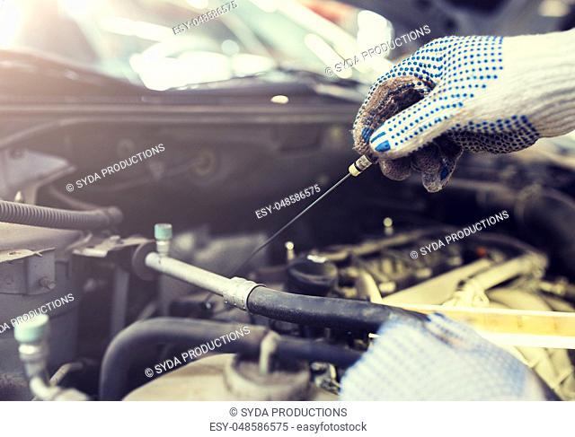 mechanic with dipstick checking motor oil level