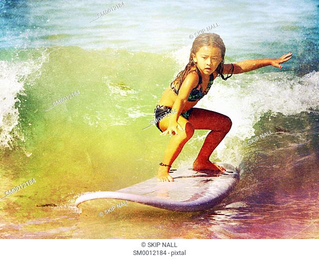 A young girl surfing a good wave