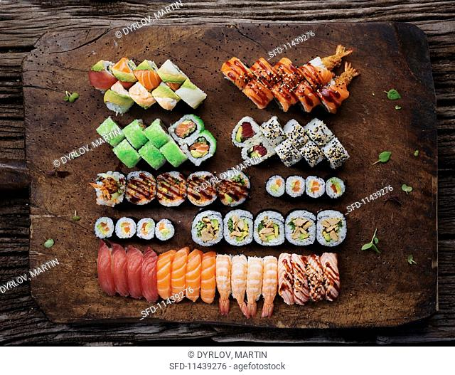Various types of sushi on a rustic wooden platter