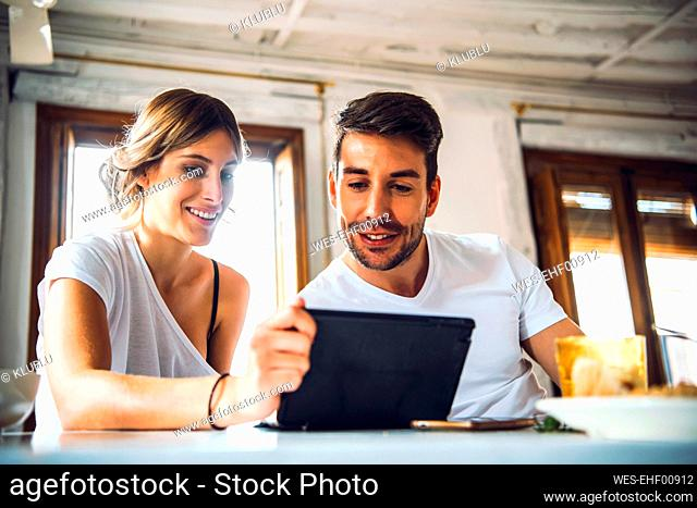 Young couple watching tablet at home
