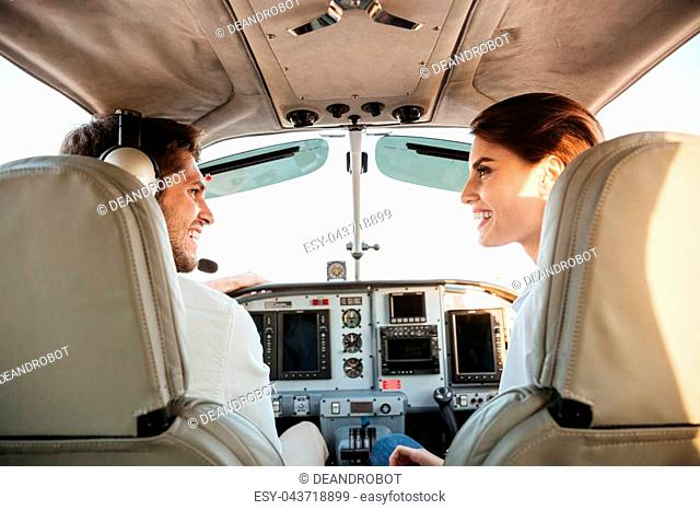 Beautiful young couple looking at each other and laughing while sitting inside airplane cabin