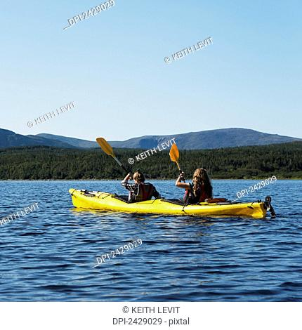 Two young women kayaking in Gros Morne National Park; Trout River, Newfoundland, Canada