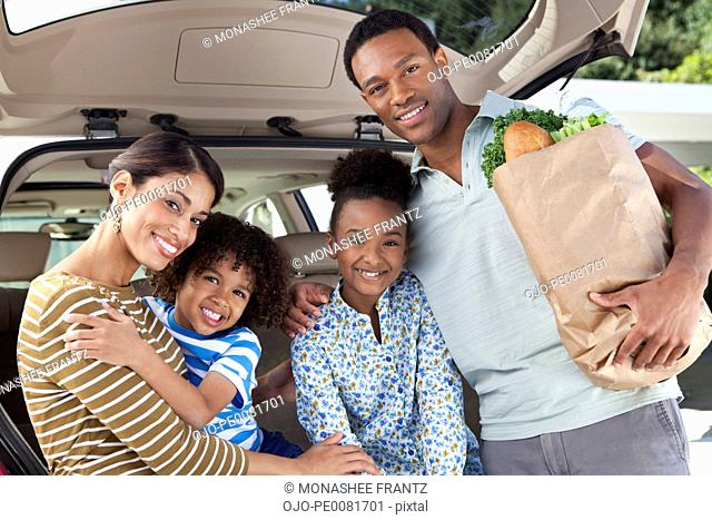 Family unloading groceries from car