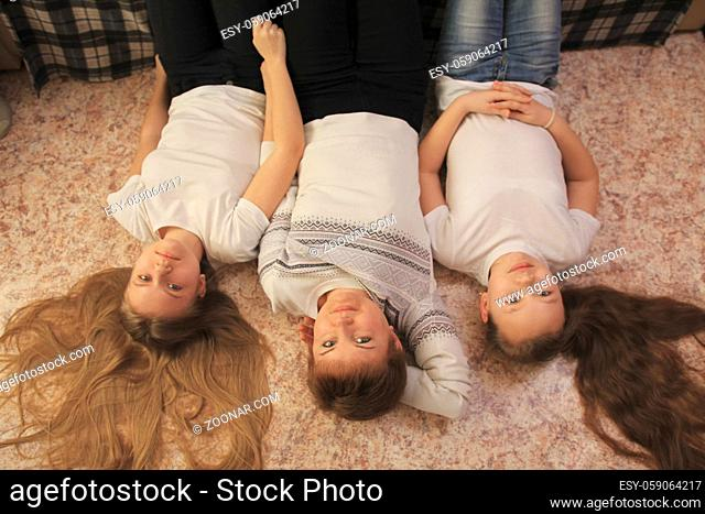 Young mom and her two teen daughters lying on the floor at home, concept of family relations