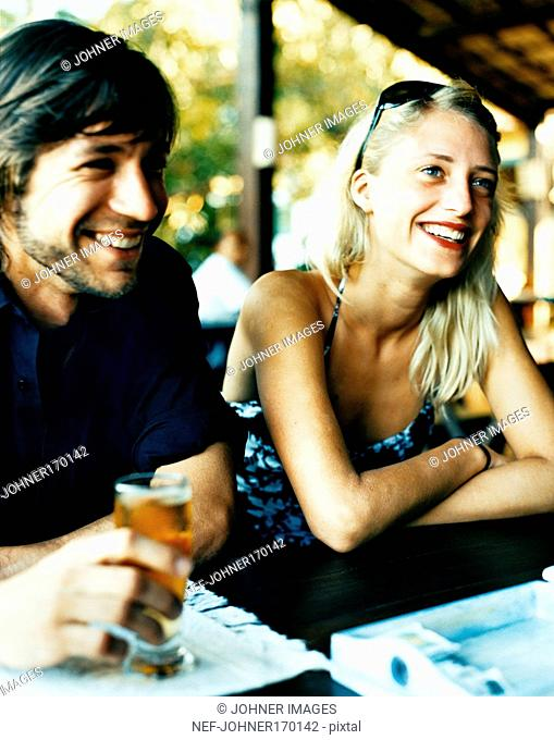 A smiling young man and woman in an open-air cafe