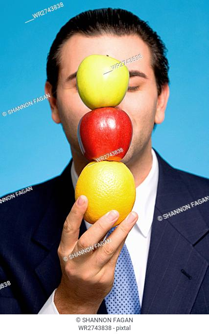 Businessman holding a stack of fruit