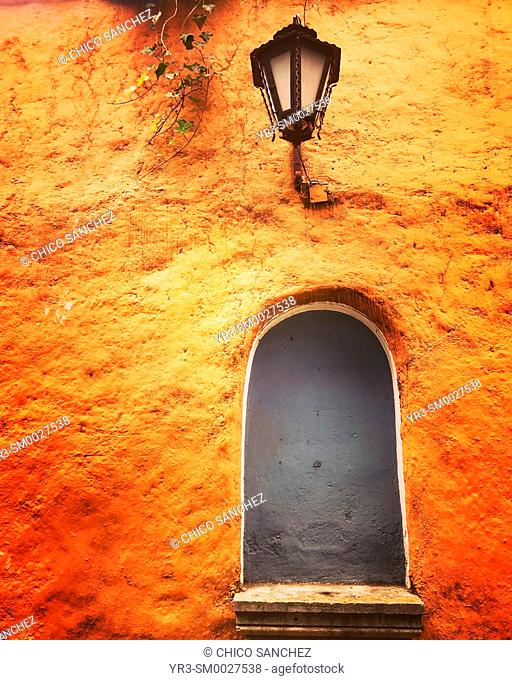 A street lamp and an empty altar in an orange wall in San Angel, Mexico City, Mexico