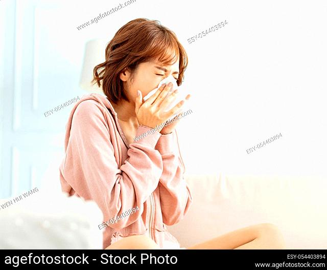 Sick young woman at home on the sofa with a cold
