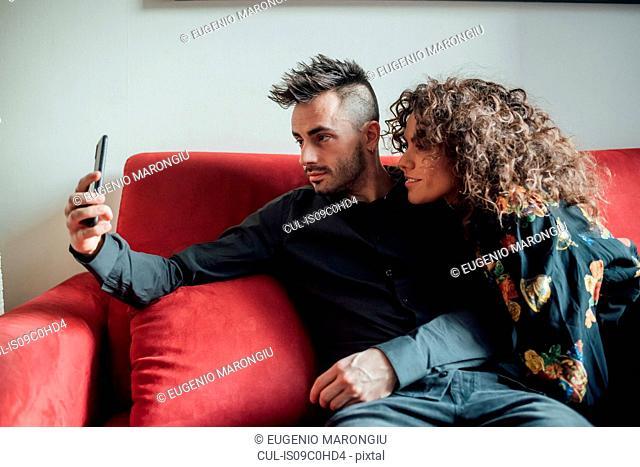 Couple taking selfie on sofa