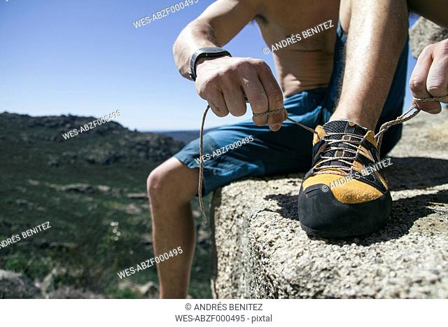 Close up of a climber tying shoelaces of his climbing shoes