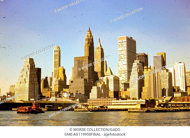 View facing west of morning sun shining on skyscrapers in lower Manhattan, New York City, August, 1966. A fire boat in the East River sprays water toward the...