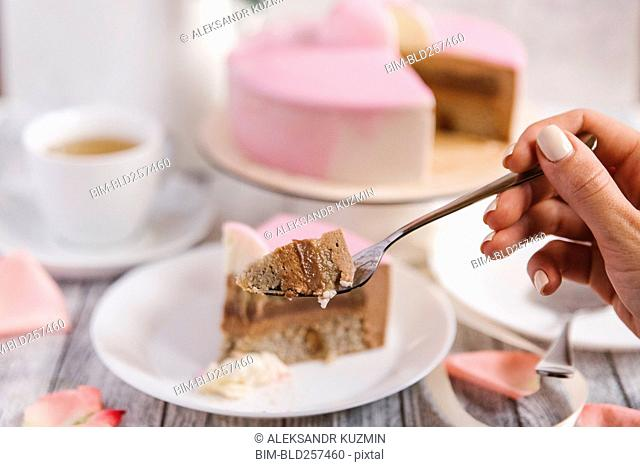 Hand of woman holding cake on fork