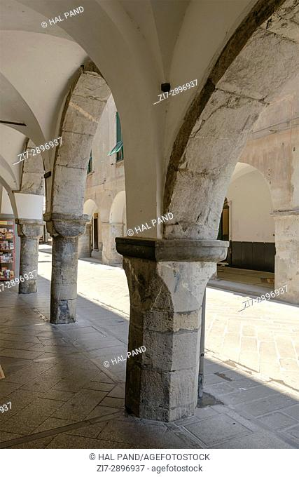 stone arches and pillars at old medieval covered walkway, shot at Mediterranean little town of Chiavari, Genova, Liguria, Italy