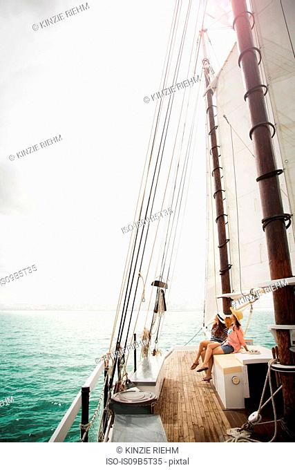 Two women on sitting on deck of sailing boat, on sea