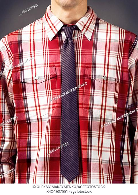 Closeup of a man wearing fancy red tartan shirt with a skinny stripy necktie