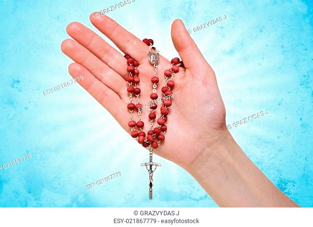 hand with rosary on blue abstract background