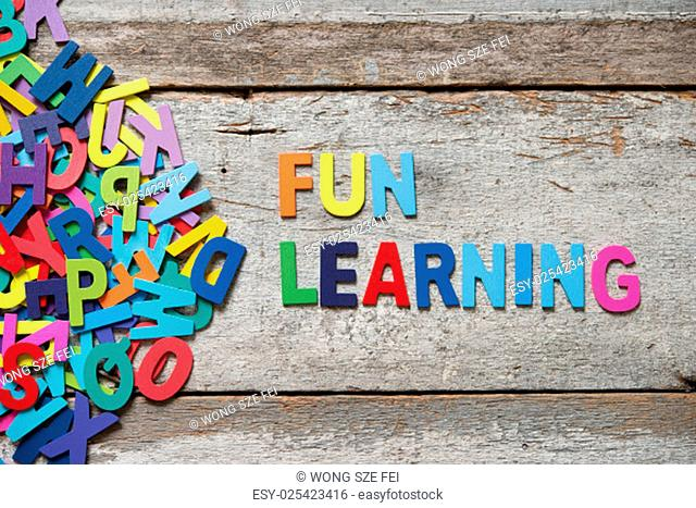 "The colorful words """"FUN LEANRING"""" made with wooden letters next to a pile of other letters over old wooden board"