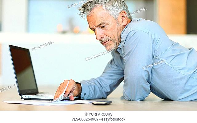 A handsome mature man looking relaxed while working at home