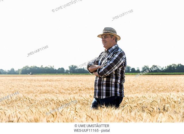 Smiling senior farmer standing in a field
