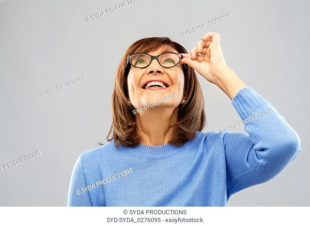 portrait of senior woman in glasses looking up