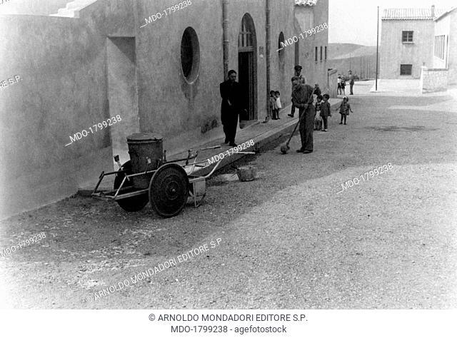 A man cleaning a street of Borgo Gattuso, now called Borgo Petilia, built during the area regeneration sponsored by the Ente di Colonizzazione del Latifondo...