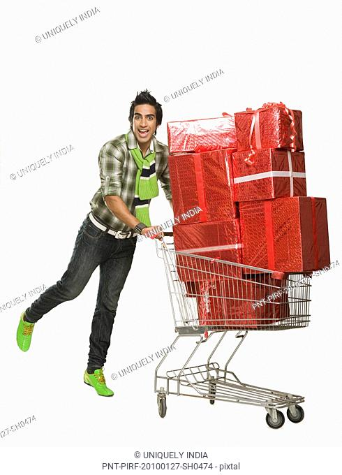 Man pushing a shopping cart filled with gifts