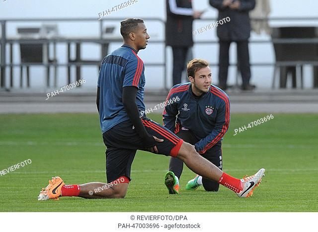 FC Bayern Munich's Jerome Boateng (FRONT) and Mario Goetze attend a Champions League training session of FC Bayern Munich at the club's training grounds in...