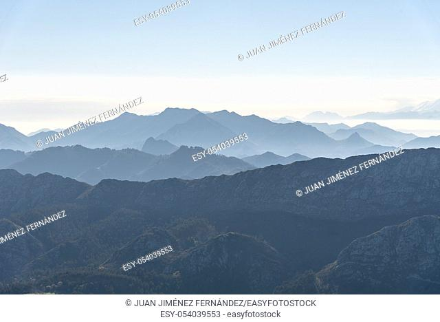 Scenic view of silhouettes of mountains in the morning mist with snowcapped mountains on background. Picos de Europa, Asturias, Spain