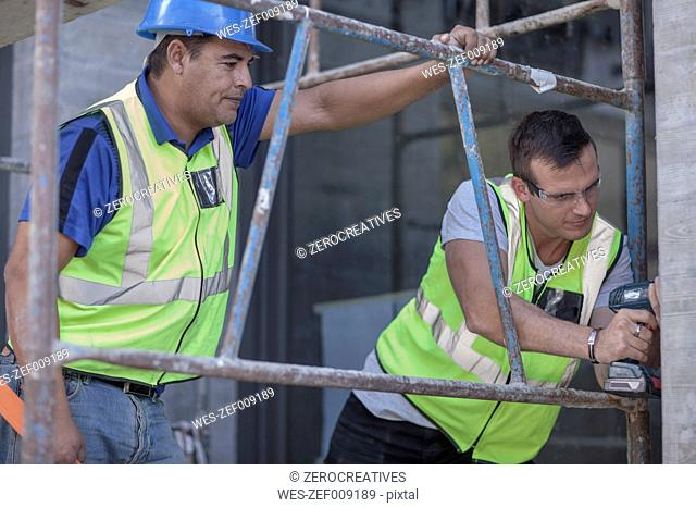 Two construction workers on scaffolding working on construction site