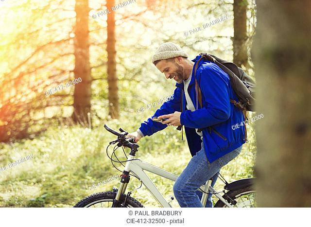 Man mountain biking texting with cell phone in woods