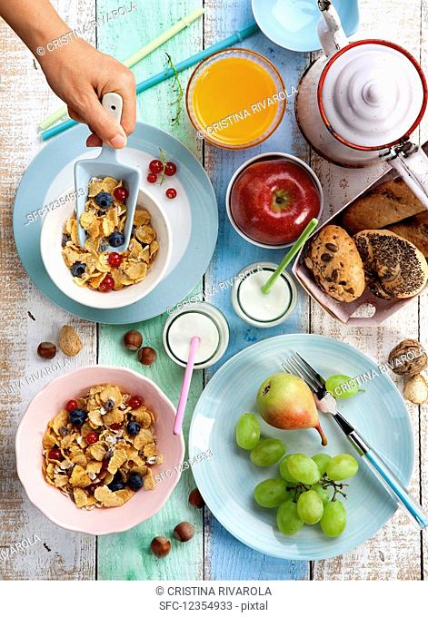 An energy food breakfast with cereals, fruit, bread rolls and juice