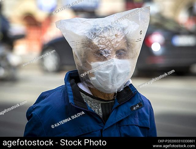 A man wearing a face mask duplicate his protection against covid-19 pandemic covering his whole head in plastic sack, Prague, Czech Republic, on March 31, 2020