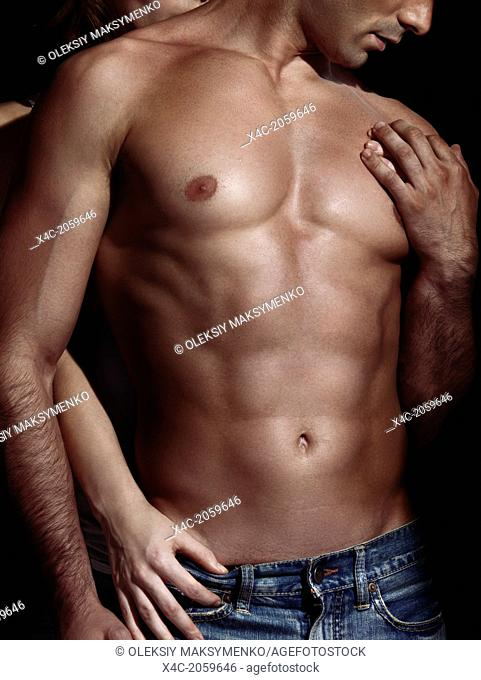 Closeup up of a woman standing behind a man with muscular bare torso dramatic sexy couple photo isolated on black background