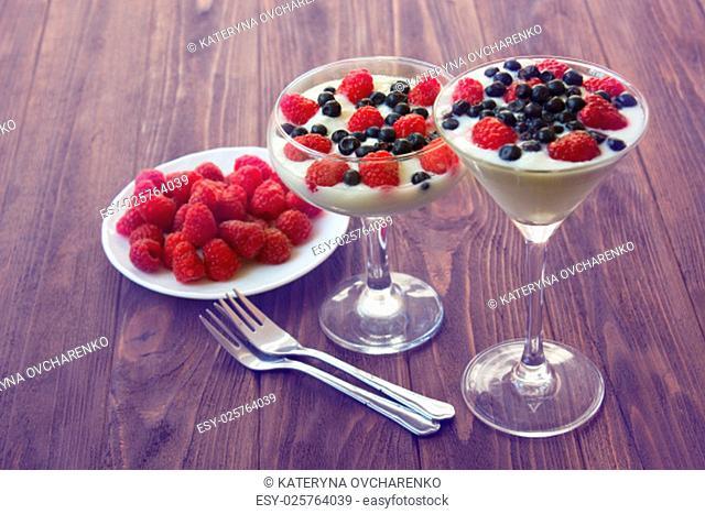yogurt dessert with raspberries and blueberries in glasses