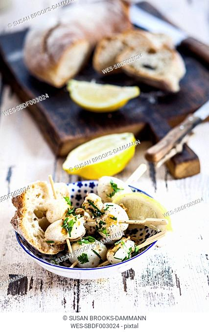 Tapas, grilled sepia, lemon and bread in bowl