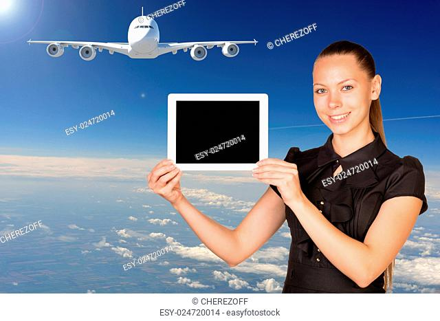 Beautiful businesswoman holding blank tablet PC. Blue sky, clowds and jet airliner as backdrop